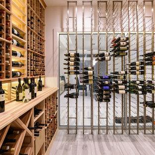 Ispirazione per una cantina design di medie dimensioni con pavimento in legno verniciato e rastrelliere portabottiglie