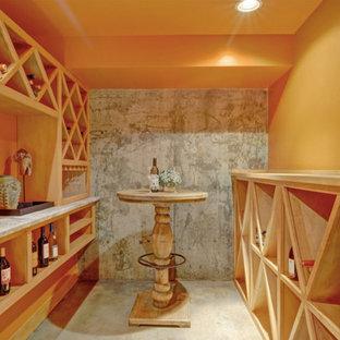 Imagen de bodega de estilo americano, pequeña, con suelo de cemento y botelleros de rombos