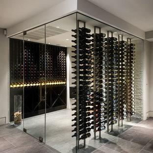 Réalisation d'une grand cave à vin design avec un sol en carrelage de porcelaine, un présentoir et un sol gris.