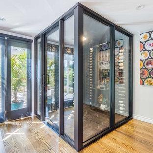 Ispirazione per una piccola cantina design con pavimento in gres porcellanato, portabottiglie a vista e pavimento nero