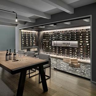 Immagine di una cantina contemporanea con portabottiglie a vista e pavimento grigio