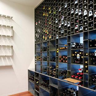 Idéer för funkis vinkällare, med mellanmörkt trägolv och vinhyllor