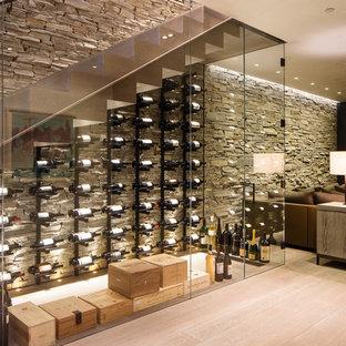 Foto på en mellanstor funkis vinkällare, med vindisplay, ljust trägolv och beiget golv