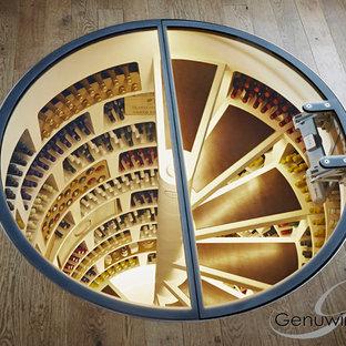 Idée de décoration pour une cave à vin design de taille moyenne avec béton au sol et des casiers.