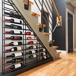 Idée de décoration pour une cave à vin design avec un sol en bois clair, des casiers et un sol jaune.