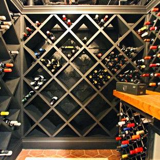Exempel på en liten industriell vinkällare, med klinkergolv i keramik och vinställ med diagonal vinförvaring