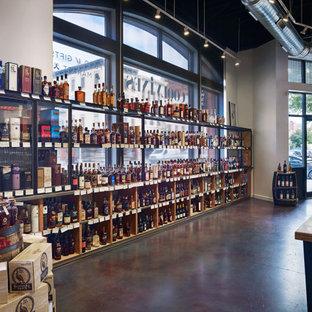 Aménagement d'une grand cave à vin contemporaine avec béton au sol, un présentoir et un sol violet.