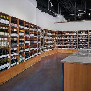 Idée de décoration pour une grand cave à vin design avec béton au sol, un présentoir et un sol violet.