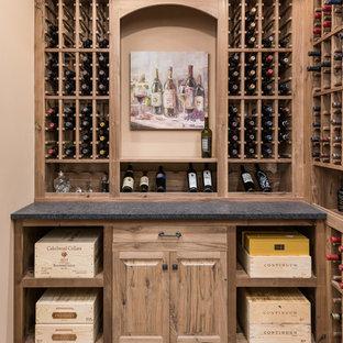Idée de décoration pour une grande cave à vin tradition avec des casiers et un sol marron.