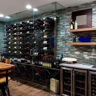 Modern inredning av en mycket stor vinkällare, med mellanmörkt trägolv, vinhyllor och brunt golv