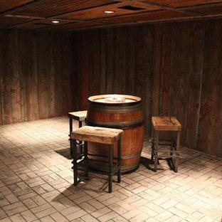 Réalisation d'une grand cave à vin chalet avec un sol en brique et un sol beige.