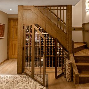 Inspiration pour une petit cave à vin traditionnelle avec des casiers, un sol en bois clair et un sol marron.