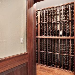 Foto de bodega de estilo americano, de tamaño medio, con suelo de madera en tonos medios y botelleros