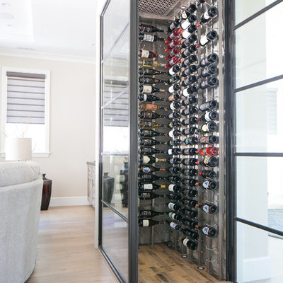 Wine cellar - small contemporary medium tone wood floor and beige floor wine cellar idea in Orange County with storage racks