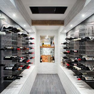 Diseño de bodega contemporánea con suelo de madera oscura y botelleros