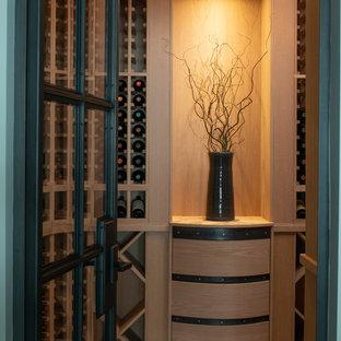 Réalisation d'une cave à vin tradition de taille moyenne avec un sol en travertin, des casiers et un sol marron.