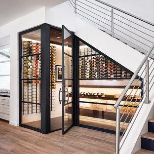 Inspiration pour une cave à vin design de taille moyenne avec un sol en bois clair, un présentoir et un sol beige.