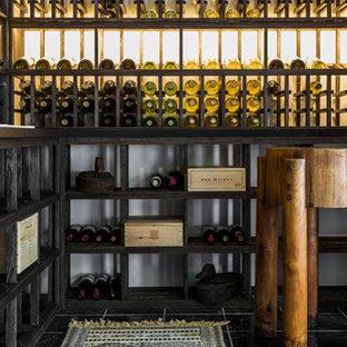 Imagen de bodega minimalista, grande, con suelo de mármol, botelleros y suelo negro