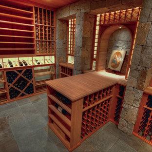 Rustik inredning av en stor vinkällare, med skiffergolv och vinhyllor