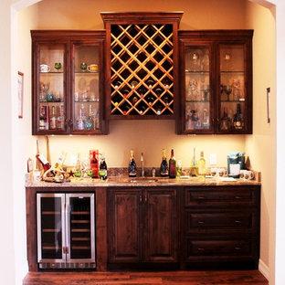 Cette image montre une cave à vin chalet de taille moyenne avec un sol marron, un sol en bois foncé et des casiers losange.