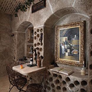 Foto de bodega mediterránea, grande, con suelo de cemento, botelleros y suelo marrón