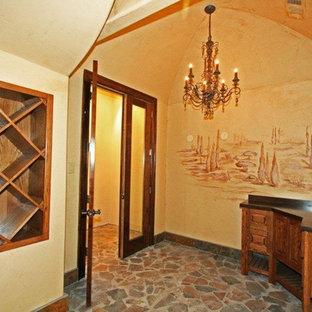 Idée de décoration pour une grand cave à vin méditerranéenne avec un sol en ardoise, des casiers losange et un sol marron.