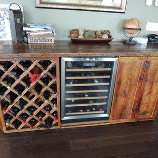 Exempel på en liten rustik vinkällare, med mörkt trägolv och vinhyllor