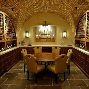Bild på en stor medelhavsstil vinkällare, med skiffergolv, vinhyllor och grått golv