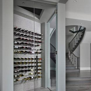 Imagen de bodega clásica renovada, grande, con suelo de madera en tonos medios, botelleros y suelo gris