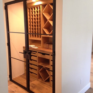 This is an example of a medium sized contemporary wine cellar in Orange County with light hardwood flooring and cube storage.