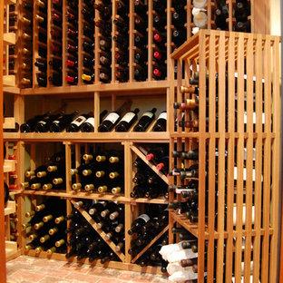 Diseño de bodega tradicional, grande, con suelo de ladrillo, botelleros y suelo rojo