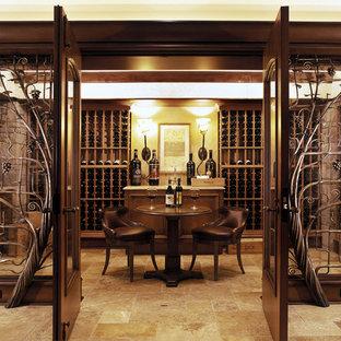 Cette photo montre une grand cave à vin tendance avec un sol en calcaire, des casiers et un sol marron.