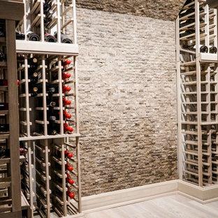 Imagen de bodega clásica renovada, pequeña, con suelo laminado, botelleros de rombos y suelo gris