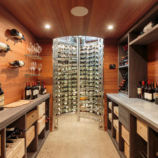 Example of a mid-sized trendy concrete floor and gray floor wine cellar design in New York with display racks
