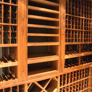 Exemple d'une cave à vin chic de taille moyenne avec un sol en bois brun et des casiers.