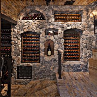 Cette photo montre une grand cave à vin méditerranéenne avec un sol en brique, des casiers et un sol multicolore.
