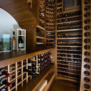 Inspiration för en liten amerikansk vinkällare, med vinhyllor och betonggolv