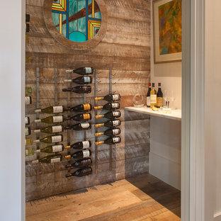 Aménagement d'une cave à vin bord de mer avec un sol en bois peint, des casiers et un sol marron.