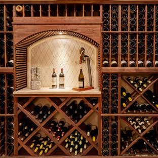 Klassisk inredning av en mellanstor vinkällare, med kalkstensgolv och vinställ med diagonal vinförvaring