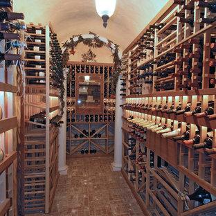 Inspiration pour une cave à vin ethnique de taille moyenne avec un sol en brique, des casiers et un sol rouge.