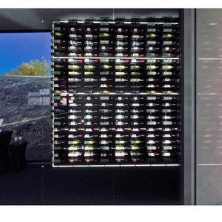 Immagine di una grande cantina contemporanea con portabottiglie a vista e pavimento nero