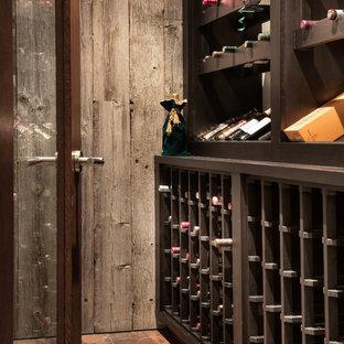 Imagen de bodega actual, de tamaño medio, con suelo de baldosas de porcelana, botelleros y suelo marrón