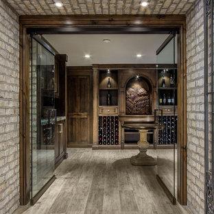 Ejemplo de bodega clásica, extra grande, con suelo de madera en tonos medios, botelleros y suelo gris