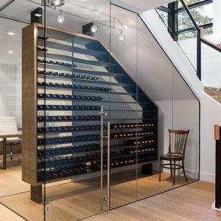 Cette image montre une petit cave à vin design avec un sol en bois clair et des casiers.