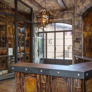 Idée de décoration pour une grand cave à vin tradition avec un sol en brique et des casiers.