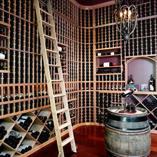 Large transitional medium tone wood floor wine cellar photo in Toronto with storage racks