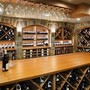Exemple d'une grand cave à vin montagne avec un sol en ardoise et des casiers losange.