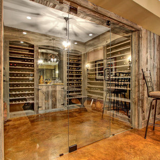 Medium sized rustic wine cellar in Other with storage racks and concrete flooring.
