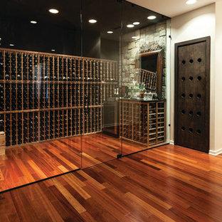 Imagen de bodega actual con suelo de madera en tonos medios, botelleros y suelo naranja
