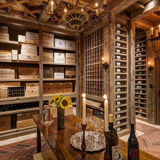 Photo of a traditional wine cellar in New York with storage racks, ceramic floors and red floor.
